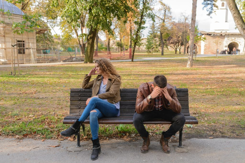 Couple sitting on a park bench ignoring each other.